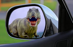 Dinosaur visible in wing mirror of car