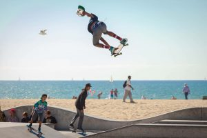 Skateboard rider jumping high in the air from a ramp on the beach front with the sea behind