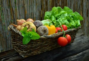 Basket full of vegetables including tomatoes, lettuce, beetroot and peppers
