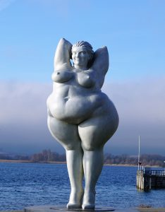 Statue of a magnificent plump lady smiling with confidence with a lake in the background