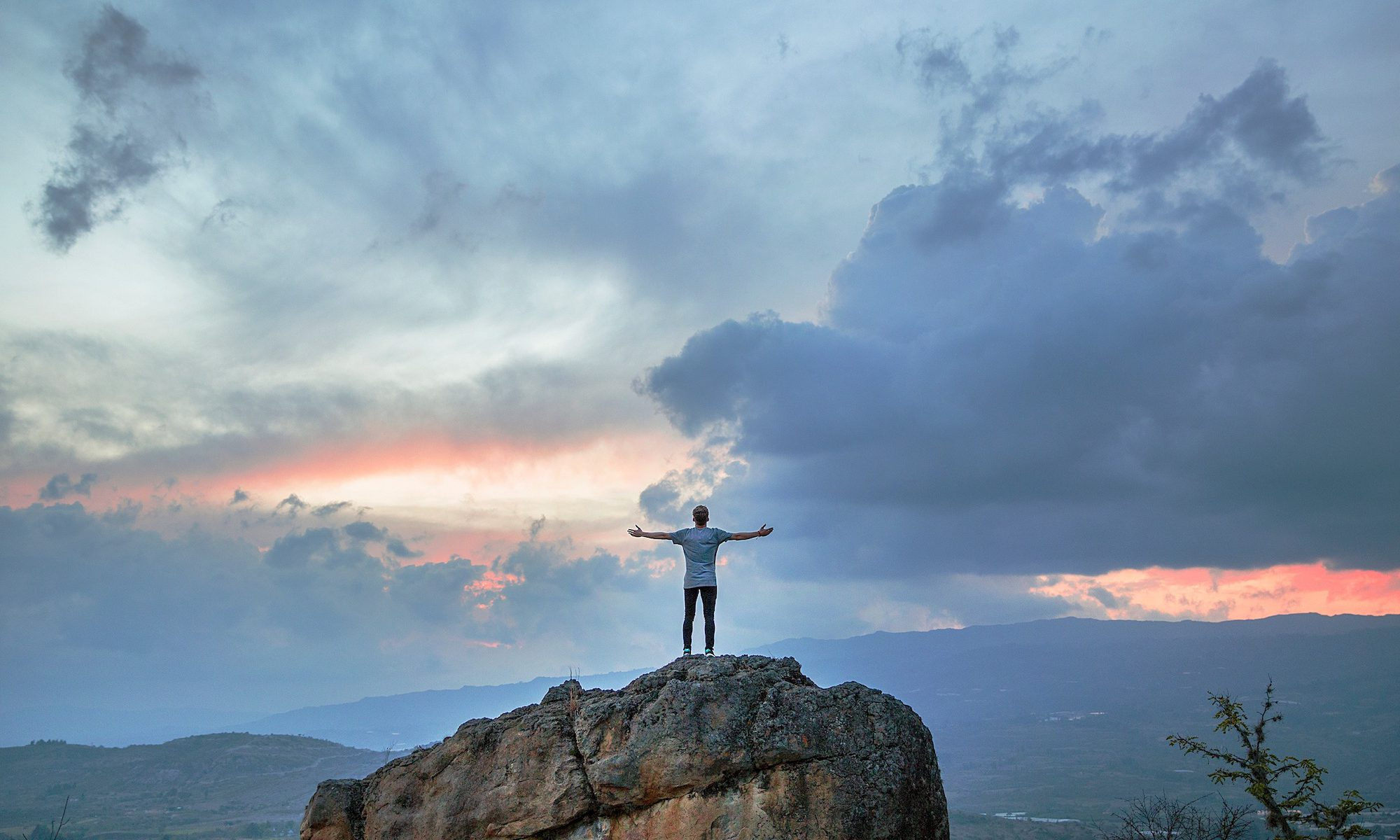 Man standing on top of a rock with his back to us, arms open wide towards the sunset
