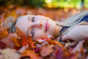 Young girl laying on the ground in autumn looking happy