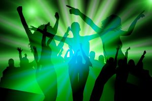 Silhuettes of people dancing with green strobe lighting behind