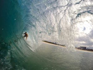 Surfer surfing through a huge roll wave