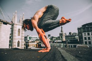 Man doing yoga on roof dressed in Ohmme yoga pants