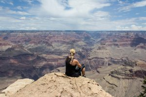 Woman sitting on rock staring out over Grand Canyon