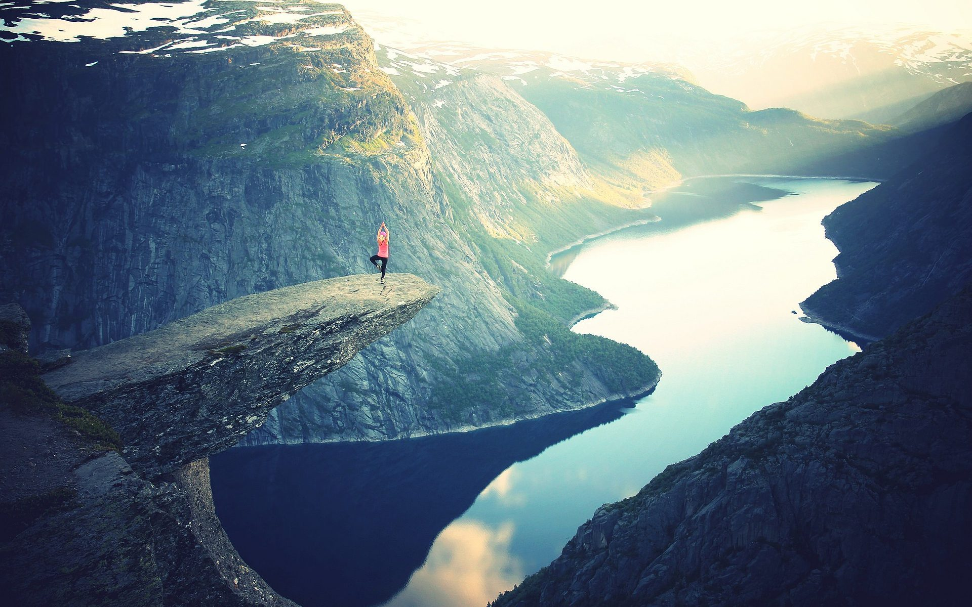 Man doing yoga on edge of rock in beautiful scenery