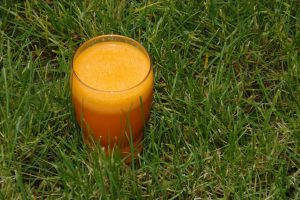 Glass of orange smoothie sitting on the grass