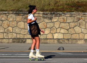 Girl carrying a bag and rollerskating down the street