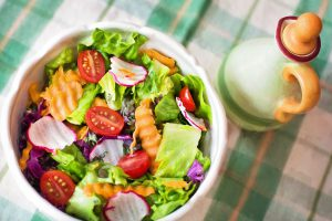 A bowl of fresh salad with dressing on the side
