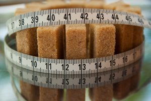Sugar cubes with a tape measure wrapped round them