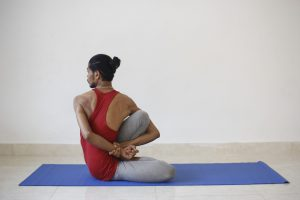 Young man doing a seated yoga pose in Ashtanga yoga.