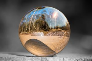 Glass ball reflecting a river bed and forest