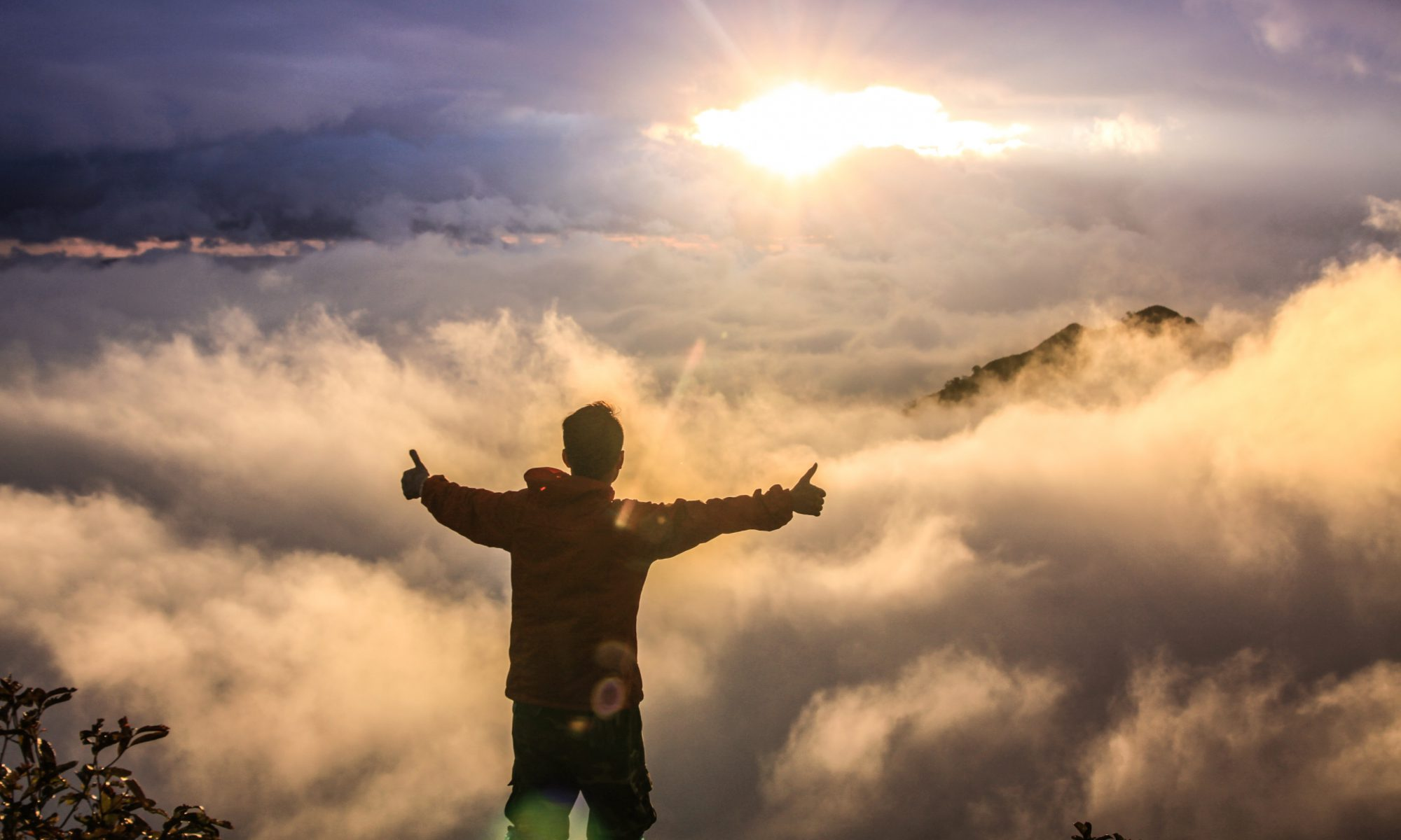 Man looking at sunrise with arms open wide