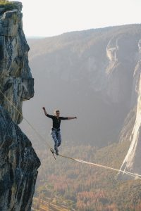 Girl walking a tightrope with mountains in the background