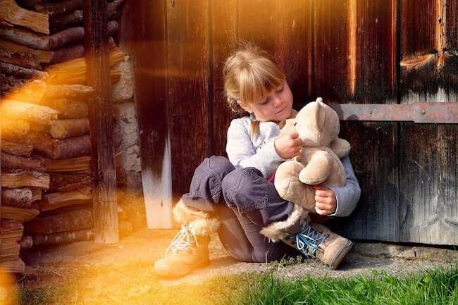 Child sitting down and cuddling a teddy bear