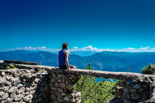 Man sitting on wall looking out over mountain view & blue skies