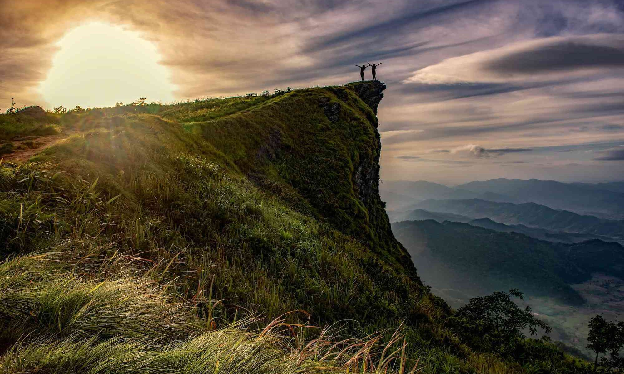 Two distant figures standing on top of a cliff