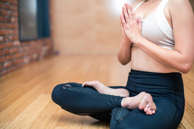 Woman sitting cross legged doing yoga